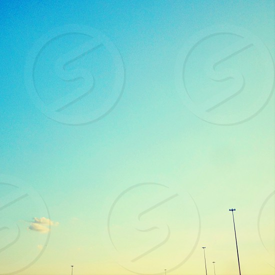 minimal sky clouds gradient blue teal green tiny light posts photo