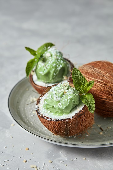 Two halves of coconut with homemade green mint ice cream green leaf on a plate on a gray background copy space.. Summer concept for vegetarian eating photo