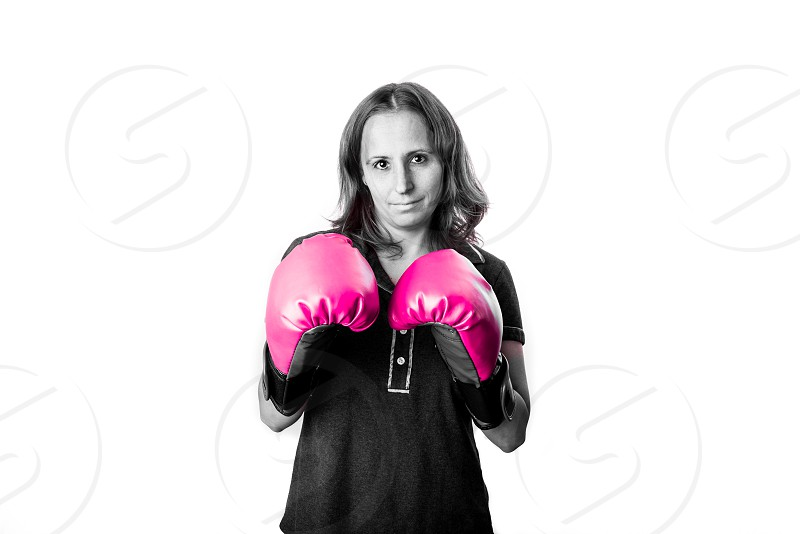 Woman wearing pink boxing gloves in a studio setting. Breast cancer awareness. Survivor. photo