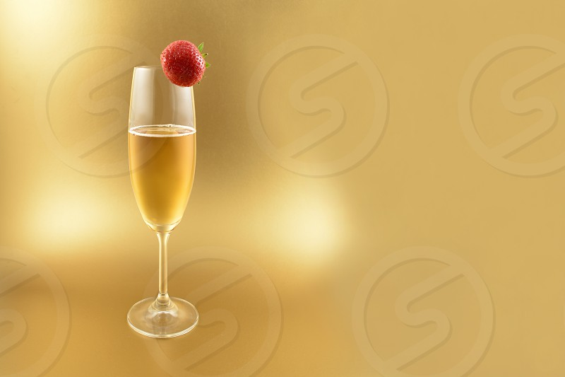 Glass of champagne with strawberry. Champagne on a golden background with copy space for text. Festive golden background photo