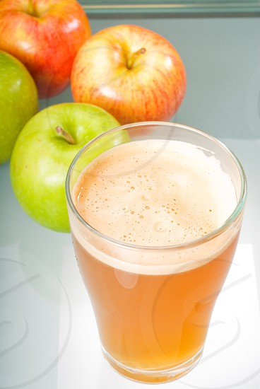 fresh  and healty natural apple  juice unfiltered  backlit on a light table photo