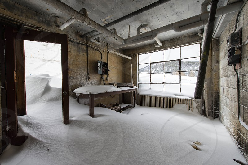 A snowdrift blows through the hospital of an abandoned town in the mountains of Colorado photo