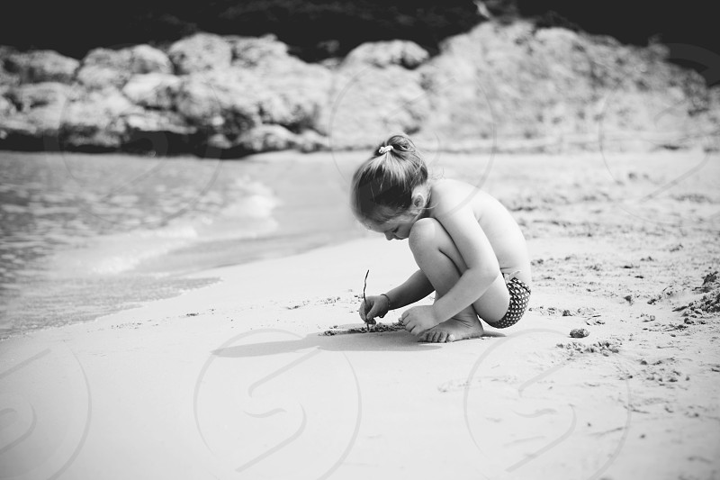 Little girl writing in sand on beach alone  in her world monochrome photograph. photo