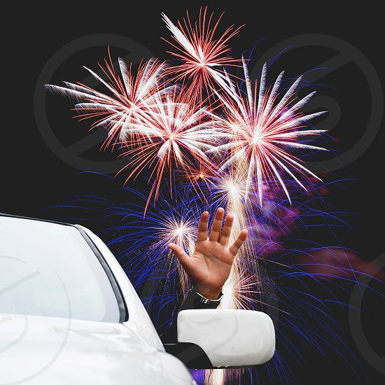 Man waving from a car window with a fireworks in the background image altered depicting a New Years eve celebration photo