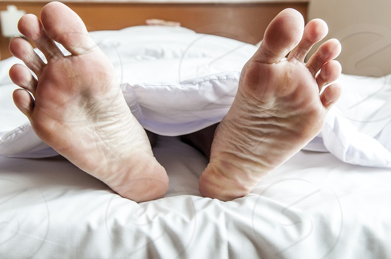 Closeup of adult male feet in bed under bed sheet photo