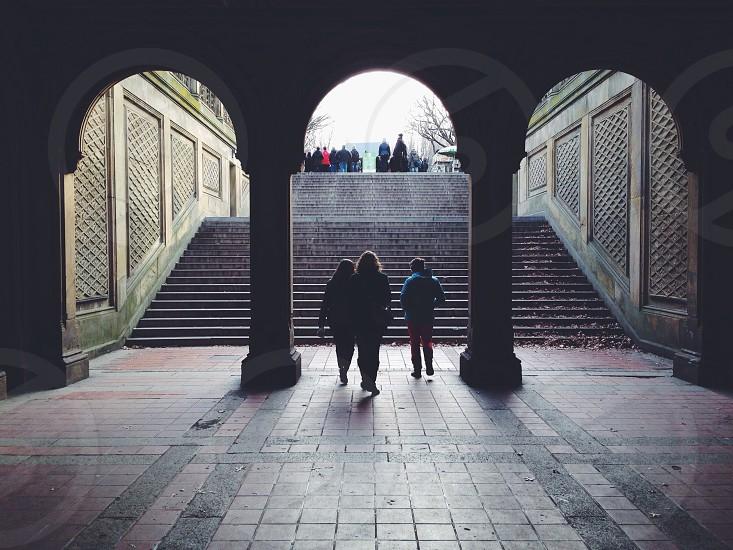 three people walking on tunnel silhouette photo