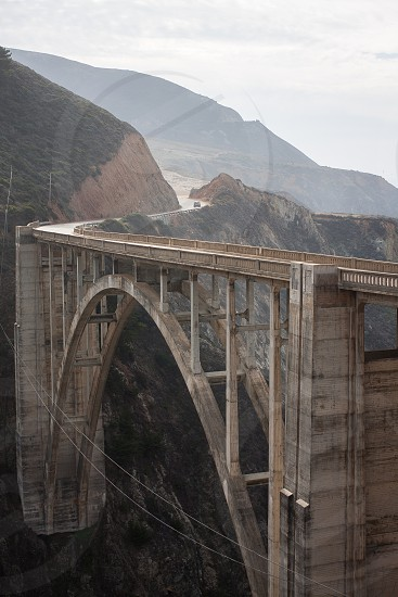 brown concrete bridge between mountains photo