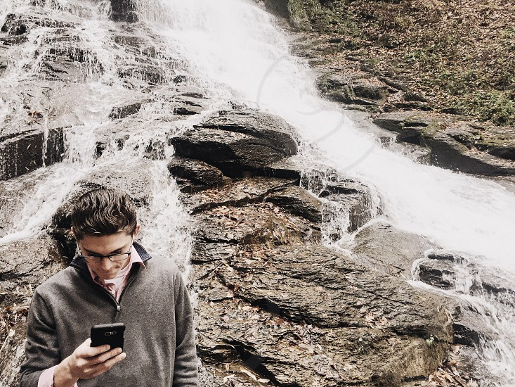 man holding smartphone in front of waterfall during daytime photo