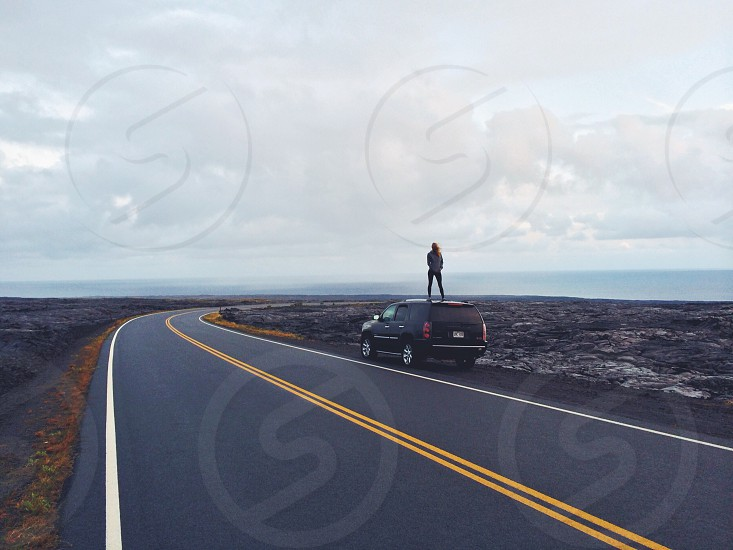 woman standing on black suv photo