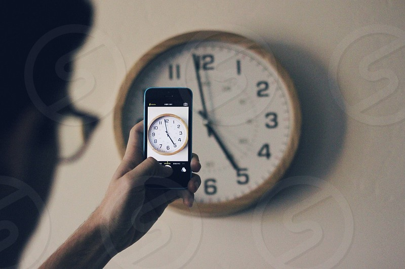 Time. Clocks. Iphone. Person taking picture  photo