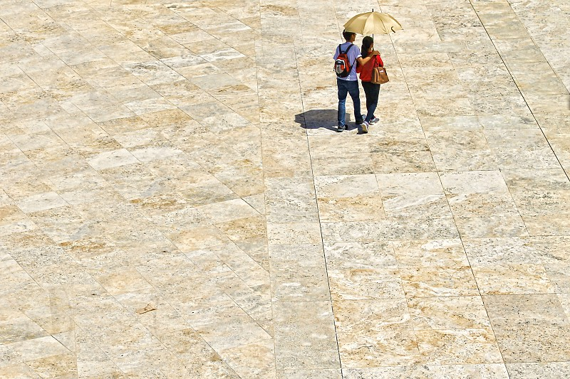 Aerial view of a couple walking across a stone plazaa photo