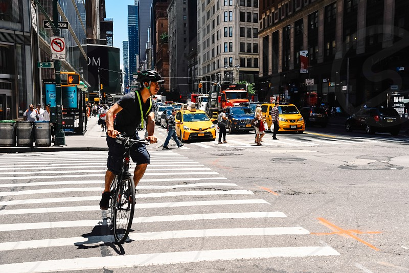 Cyclist riding by 8th Avenue against cityscape photo