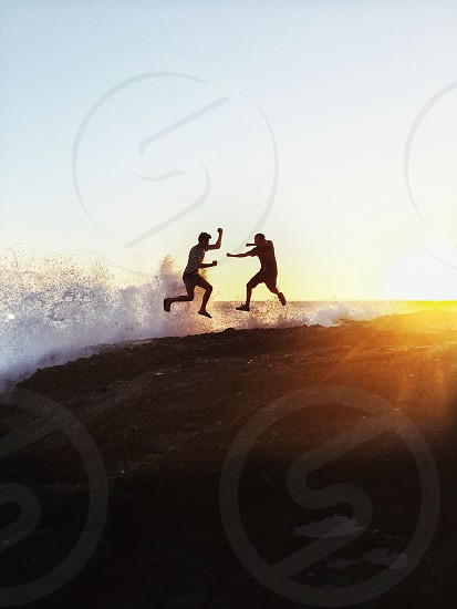 2 people silhouette fighting on seashore during daytime photo