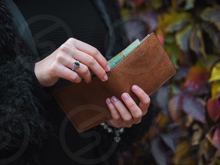people saving and finance concept - hands with cash money and wallet in autumn park. Close up hands of young woman with brown purse. photo