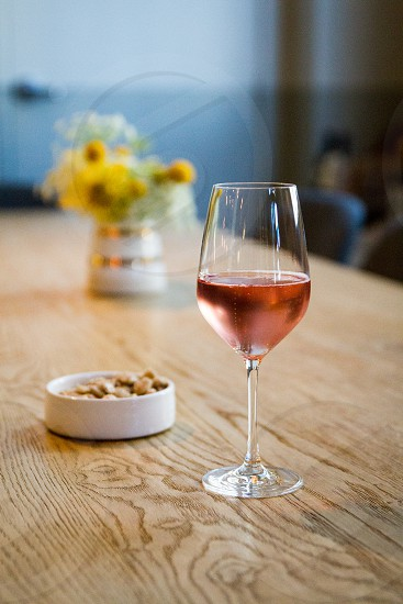 focus photography of clear wine glass with red beverages near to brown peanut on white ceramic bowl on brown wooden table photo