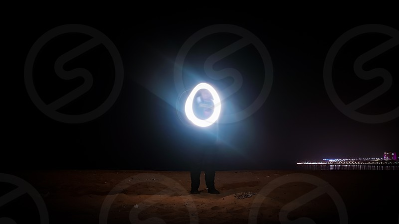 Long exposure of a man creating a circle of light photo