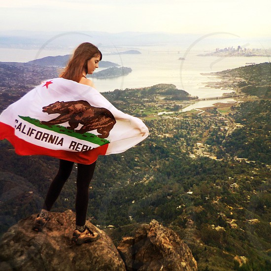 woman holding california republic flag at top of mountain view  photo