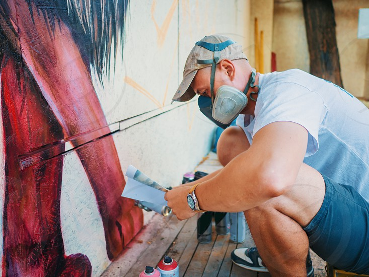 Street artist painting colorful graffiti on generic wall - Modern art concept with urban guy performing and preparing live murales with red aerosol color spray. photo
