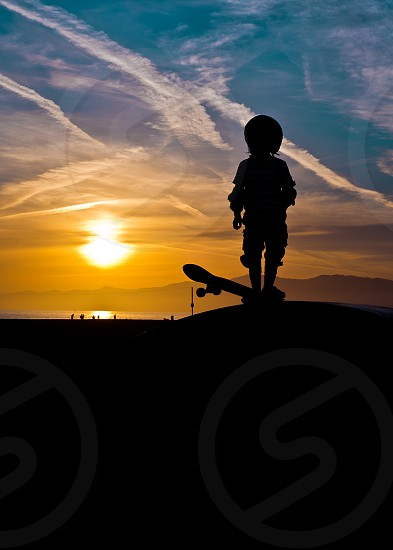 Unknown skateboarder watches the sunset at Venice Beach Skatepark in Venice Beach California. photo