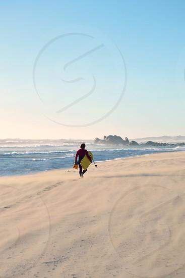 Bodyboarder on a deserted beach photo