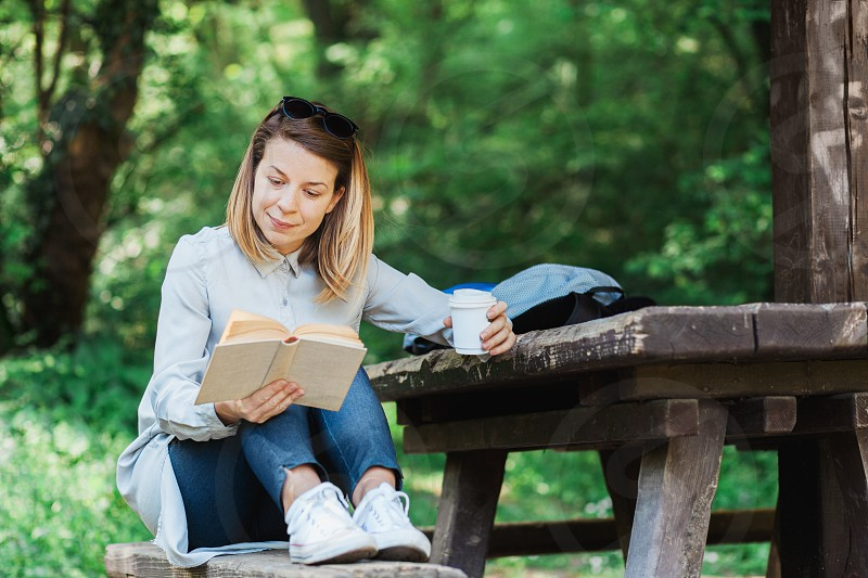 Young woman reading a book in the park photo