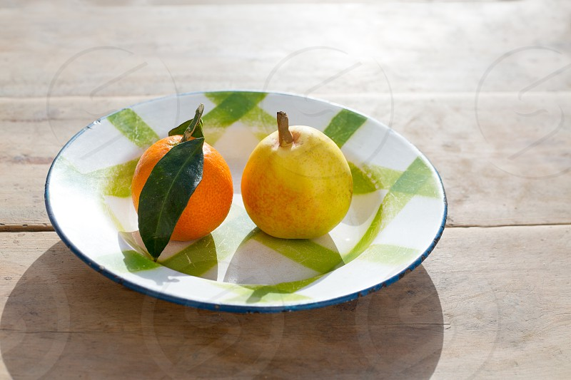 fruits tangerine and pear in vintage porcelain dish plate on retro wood table photo