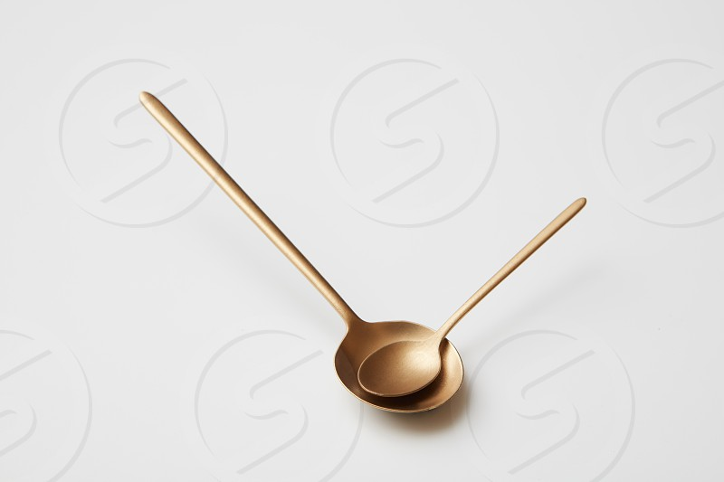 Big and small metal golden spoon isolated on gray background. Time to eat Spoons in the form of arrows on the watch photo