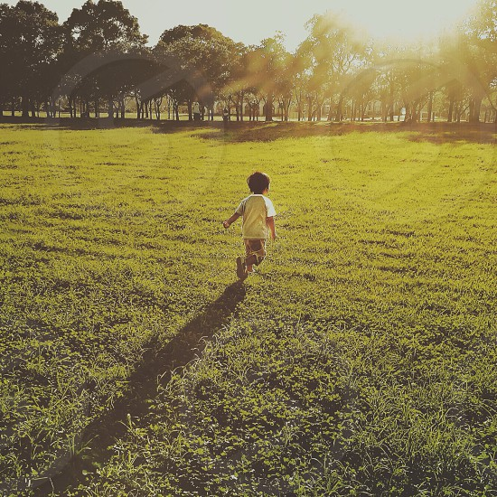 baby in white shirt walking on greenfield photo