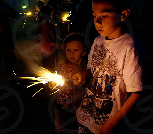 Two children stare at a sparkler on the 4th of July. photo