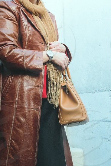 Elegant woman wearing silver wristwatch and brown leather coat holding leather brown handbag. Standing in front of blue wall photo