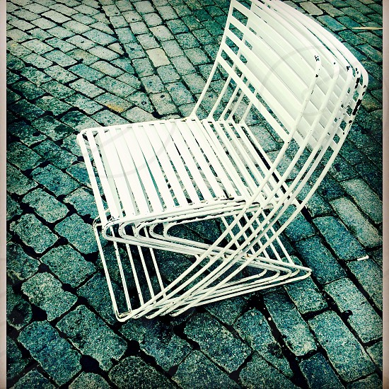 Chairs cyan cobblestone street gritty wire stackable white slats bricks linear lines repetition  photo