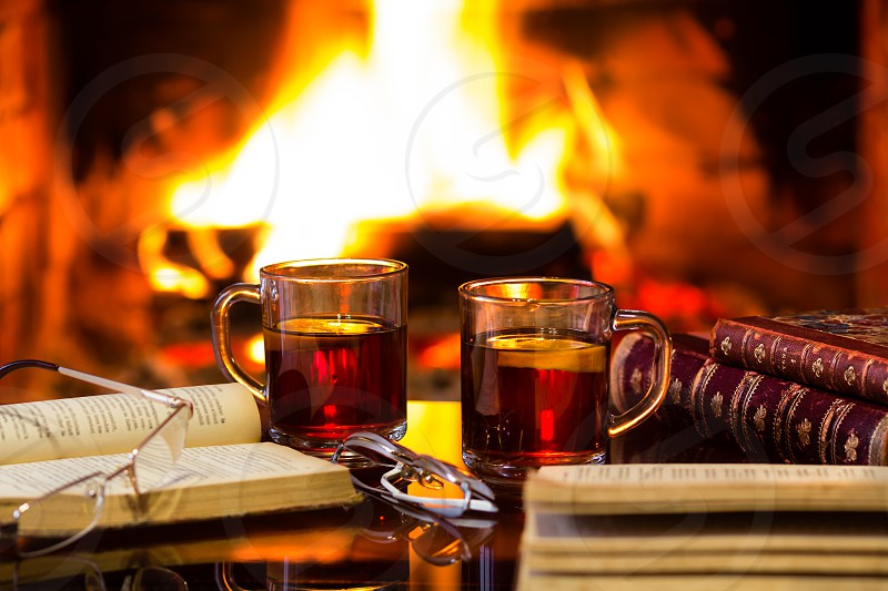 Two glass mugs of hot drink or alcoholic drink or mulled red wine and antique books in front of warm fireplace. Magical relaxed cozy atmosphere near fire. Autumn or winter concept photo