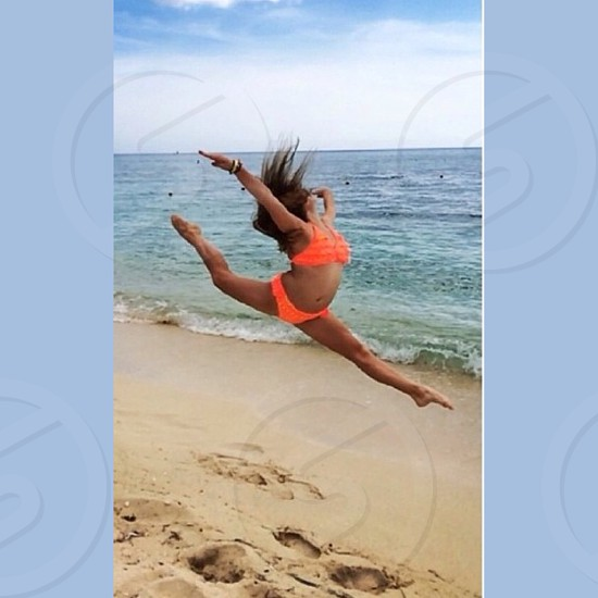 Dancer leaping on the beach in Cancun Mexico photo