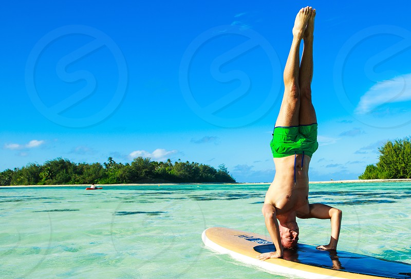 topless man wearing green shorts head standing on blue brown surfboard on water photo