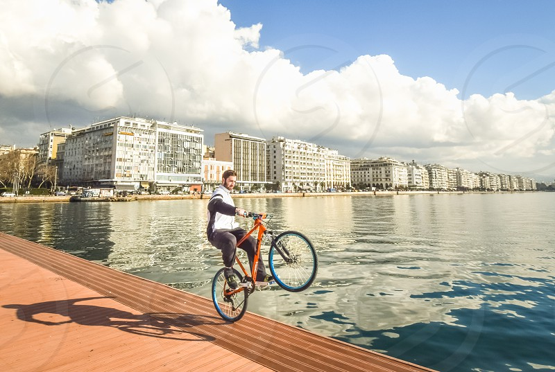 Teenager Boy Performing A Wheelie With His Bike In Front Of The Sea At The Dock photo
