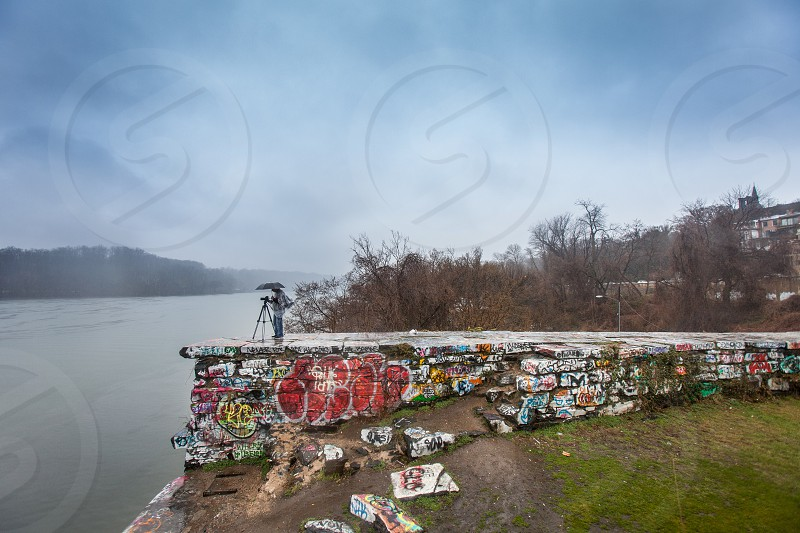 A photographer videographer stands under an umbrella while shooting in the rain. River bank trees graffiti spray tag showers storm dark urban park photo