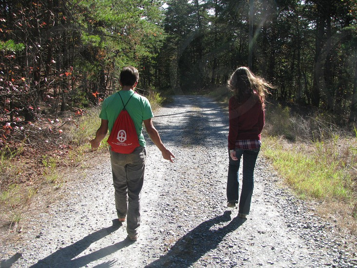 man and woman walking on dirt road beside trees during daytime photo