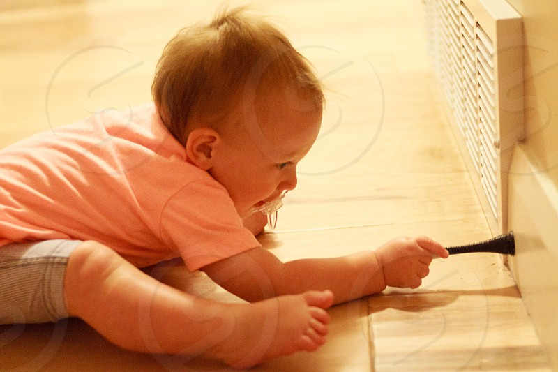 child in pink t shirt and grey shorts playing black stick on wall photo