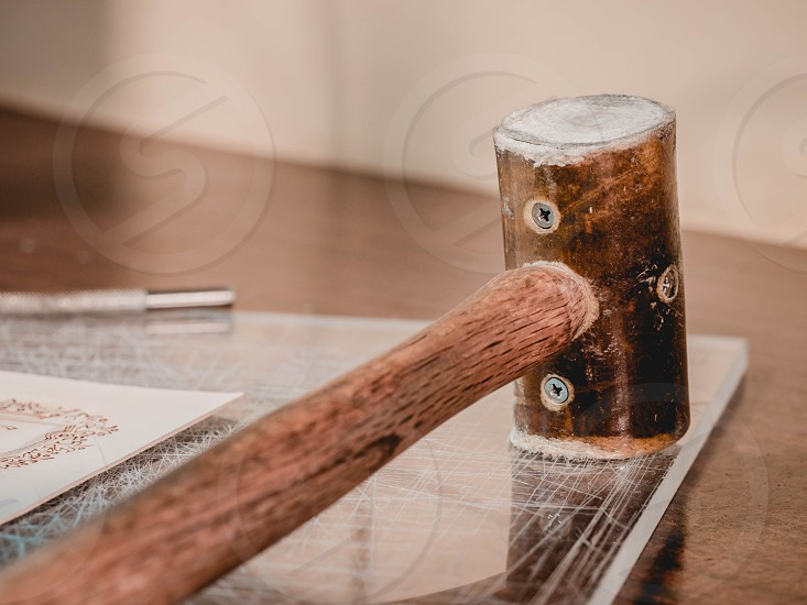 wooden hammer lies on the table in a leather processing workshop. Tool for processing natural materials photo