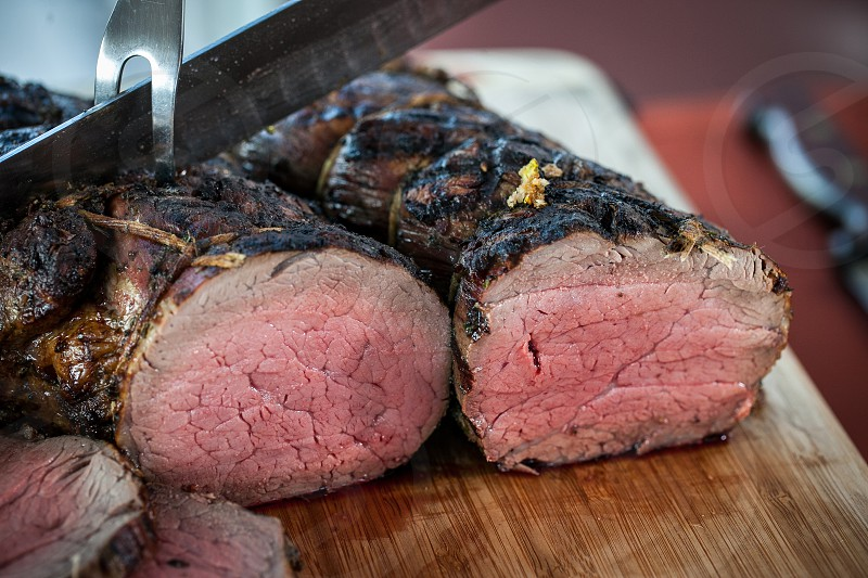 Chef cuts into a beef fillet log. photo