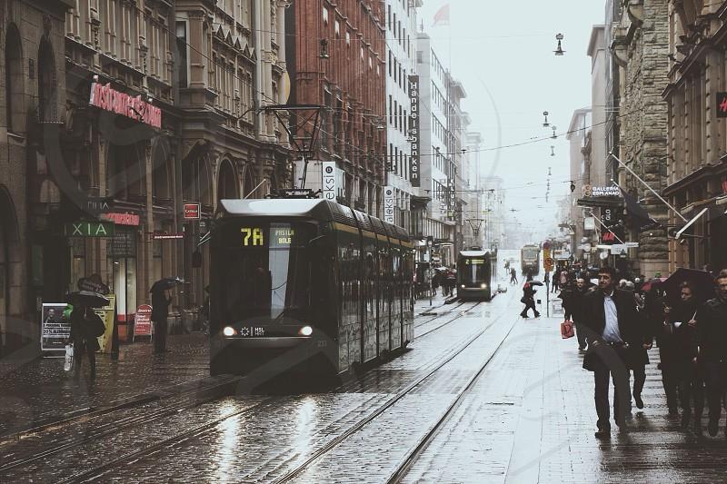 black train on railroad beside people walking on pathway near high rise buildings photo