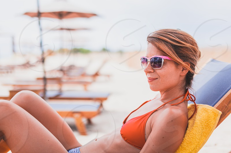 Young woman sunbathing on the beach photo