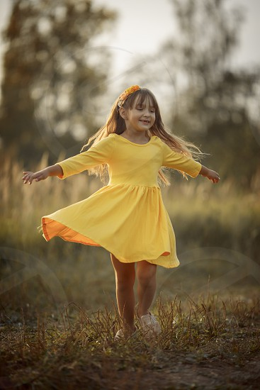 Little girl in yellow dress at autumn park photo