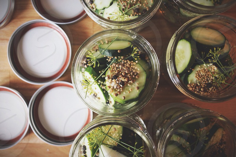 green sliced pickles inside clear glass jar photo