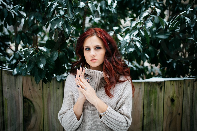 Woman standing in front of a fence and green leaves with snow on them. Red hair. photo