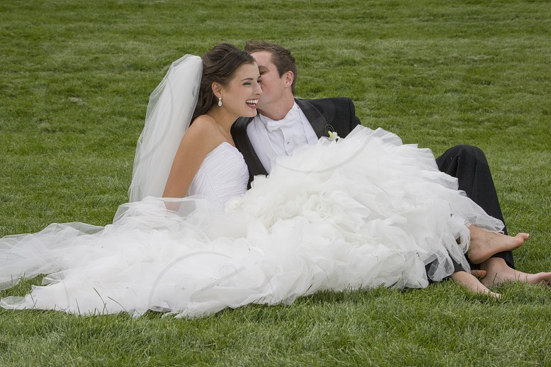 Bride and groom relaxing and cuddling on grass photo