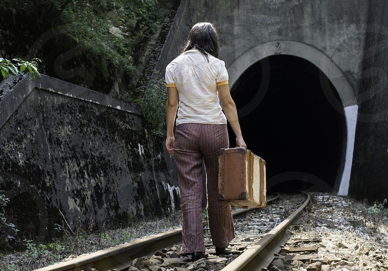 Woman and vintage suitcase on railway road and tunnel.  photo
