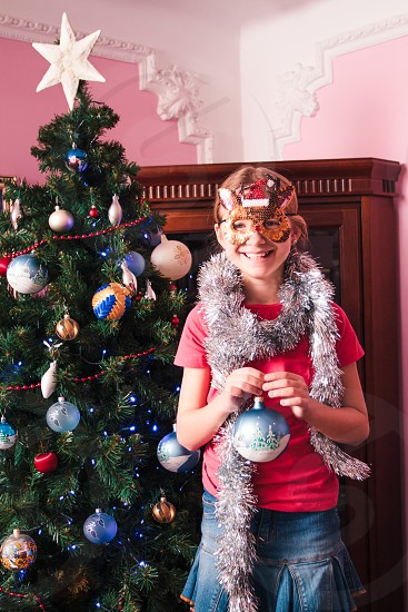 Young girl decorating Christmas tree holding big Christmas ball. Teenage blonde girl wearing blue jeans skirt and pink blouse and tights. Girl has a funny reindeer mask on her face. Young girl celebrating Christmas at home photo