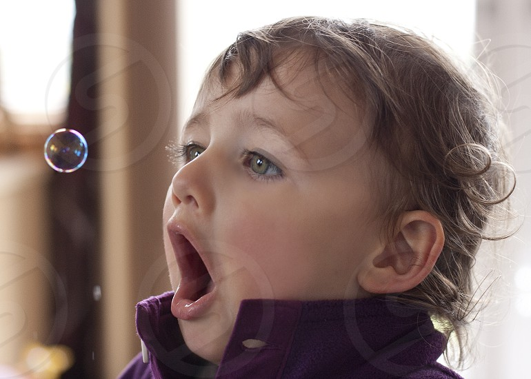 Toddler having fun with a soap bubble photo
