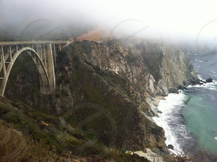 white metal bridge on mountain photo